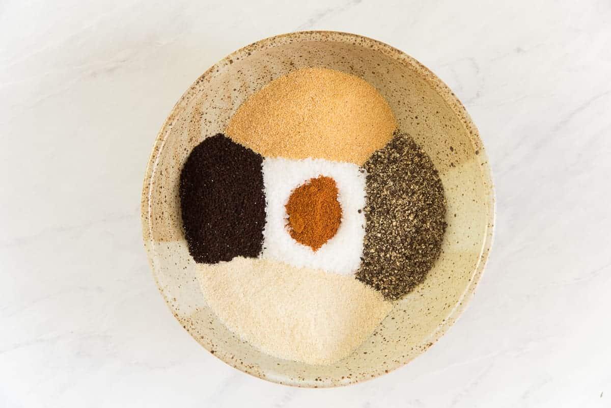 The ingredients for the coffee spice rub in a brown ceramic bowl.