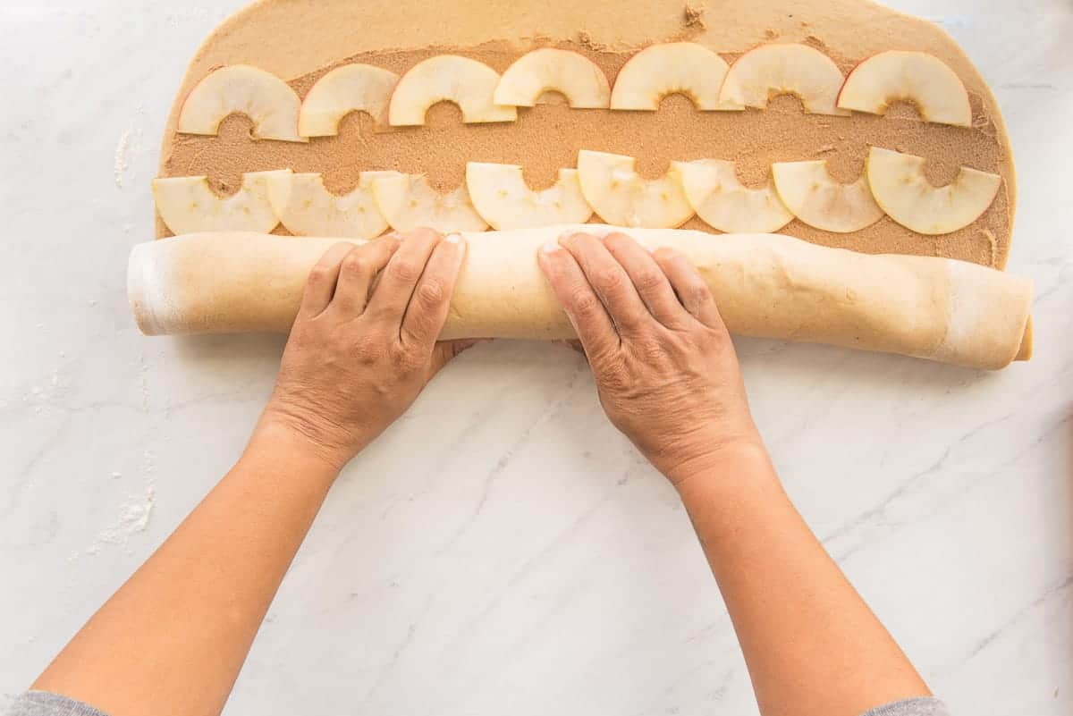 Two hands roll the dough into a log shape.