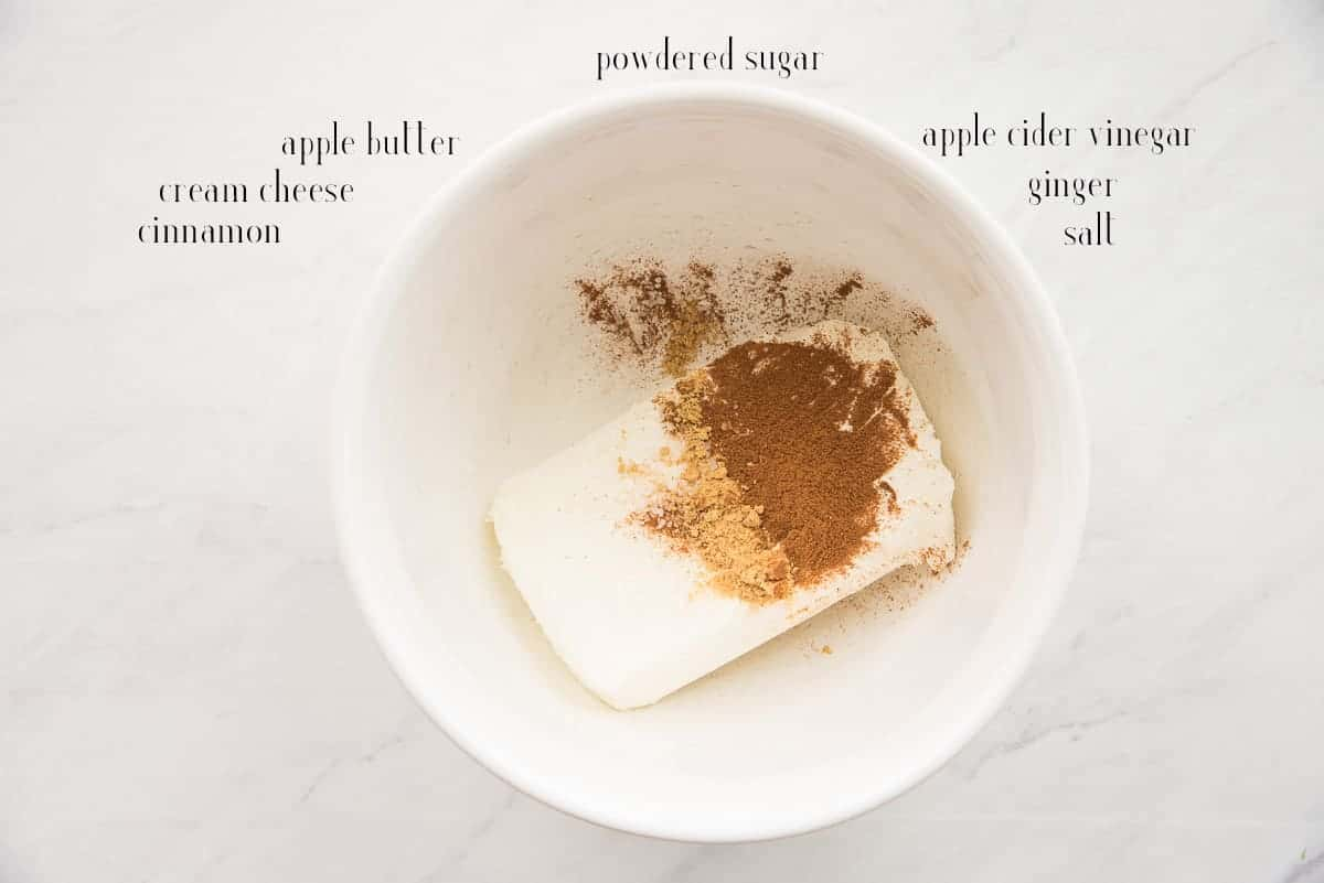 The ingredients to make the Apple Butter Cream Cheese Glaze on a white countertop: cinnamon, cream cheese, apple butter, powdered sugar, apple cider vinegar, ginger, and salt