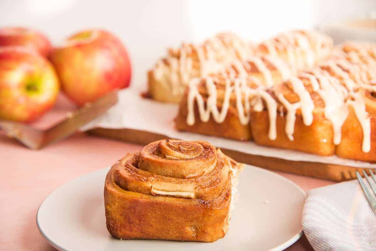 Social media image of a single, unglazed Apple Cinnamon Roll on a light grey plate in front of a batch of rolls drizzled in Apple Butter Glaze