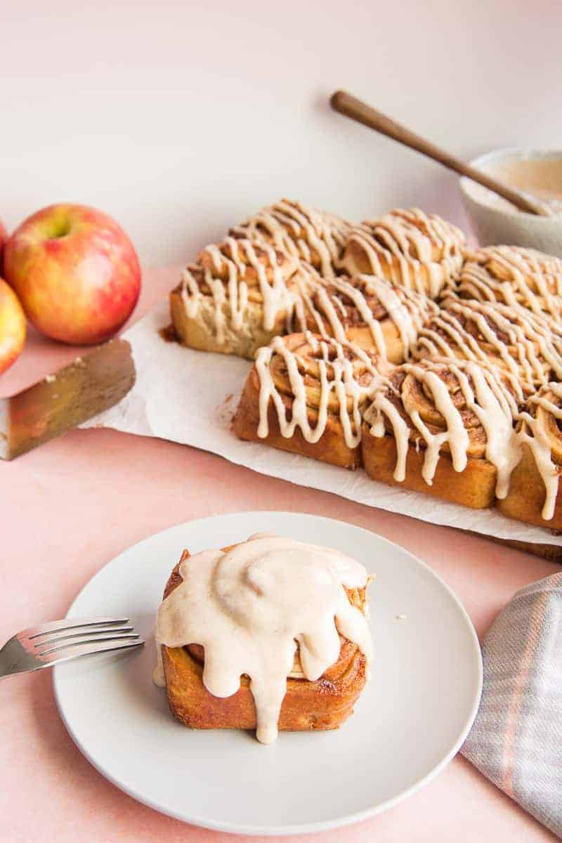 3/4 image of a single Apple Cinnamon Roll on a light grey plate in front of red apples and a batch of cinnamon rolls.