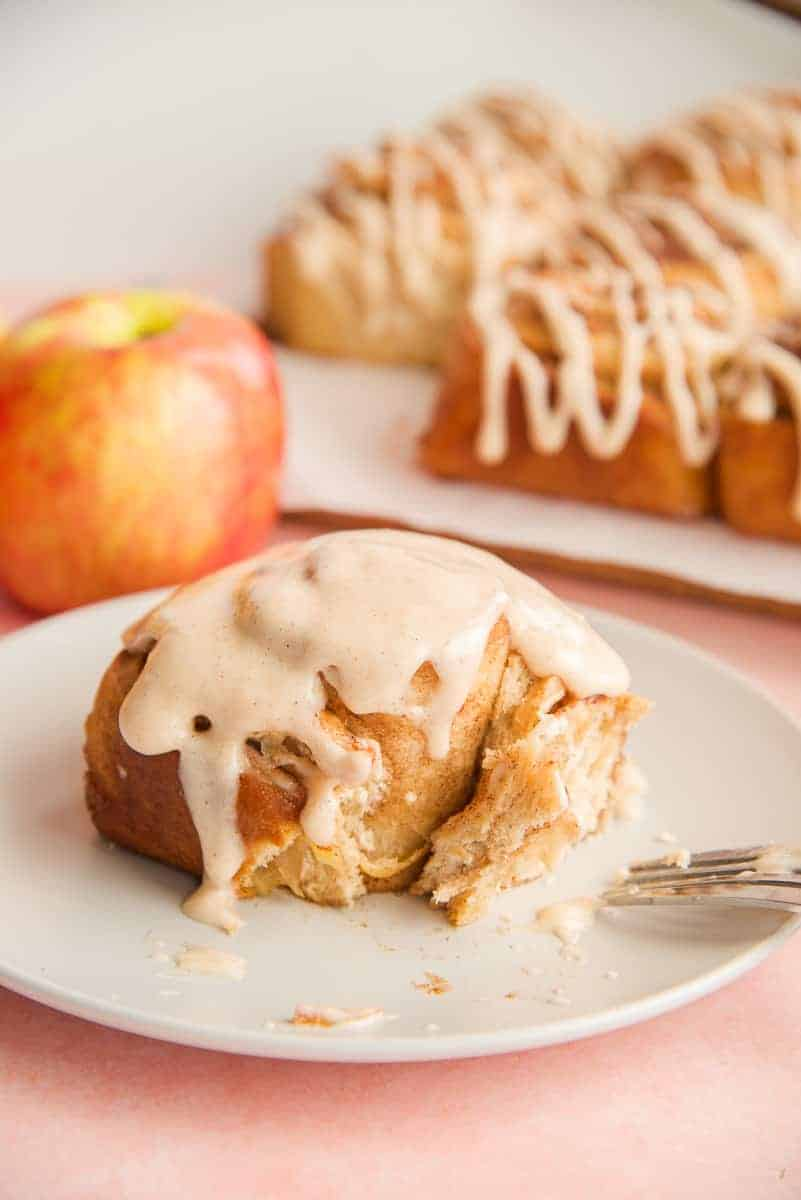Portrait image of an Apple Cinnamon Roll with Apple Butter Glaze on a grey plate with a forkful removed.