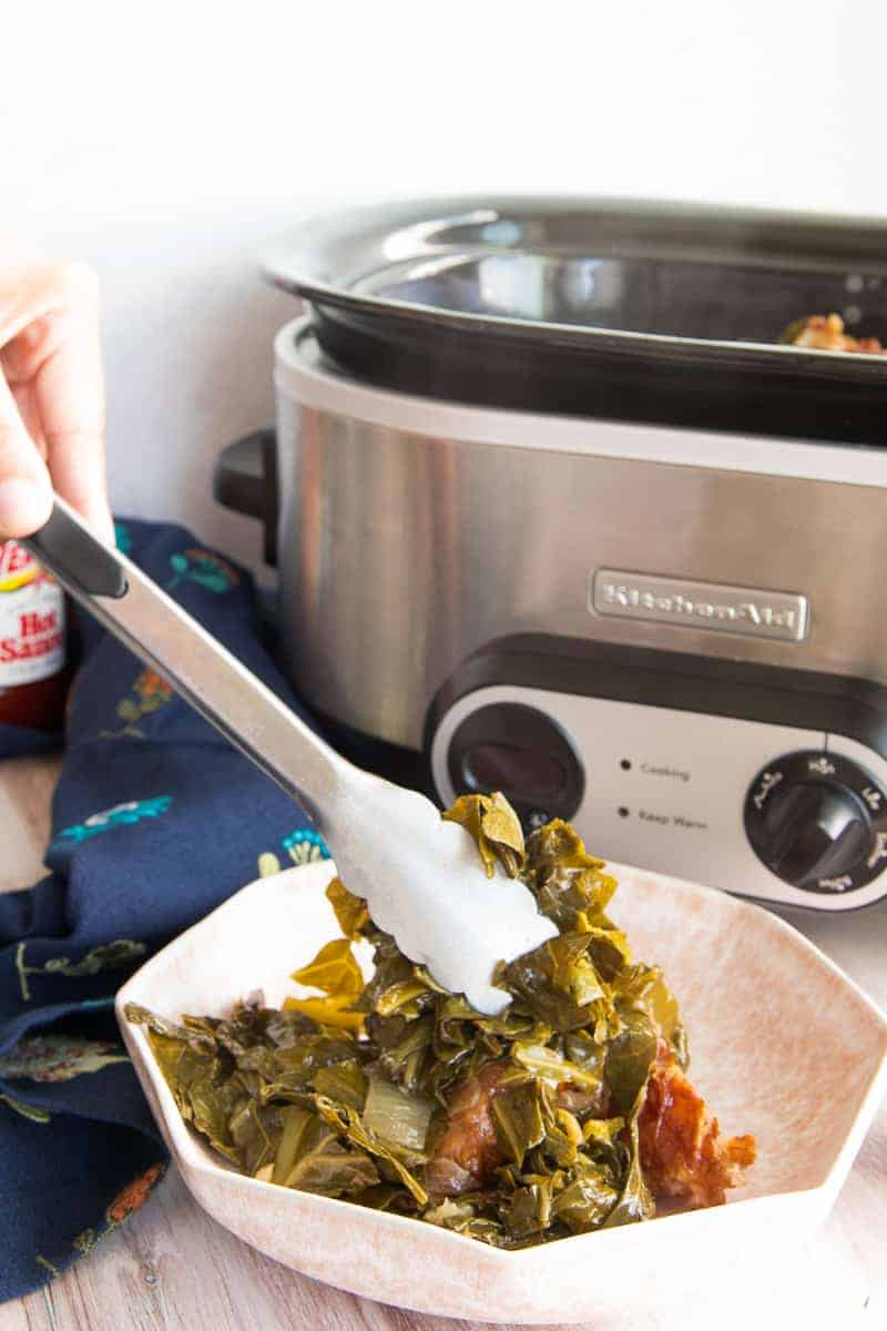 A hand uses silver tongs to serve the greens from the slow cooker into a pink bowl.