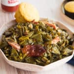 Horizontal image of a pink bowl of slow cooker collard greens in front of a bottle of red hot sauce.