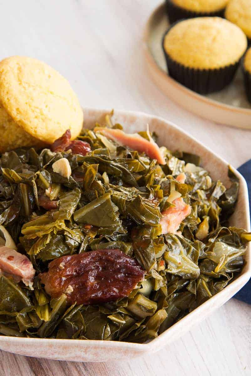 Close up portrait image of a pink bowl of slow cooker collard greens with a cornbread muffin perched on the side of the bowl.
