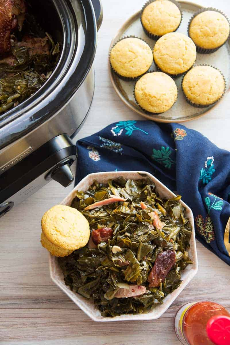 Portrait image of a pink bowl of country style collard greens next to a slow cooker and a plate of cornbread muffins.