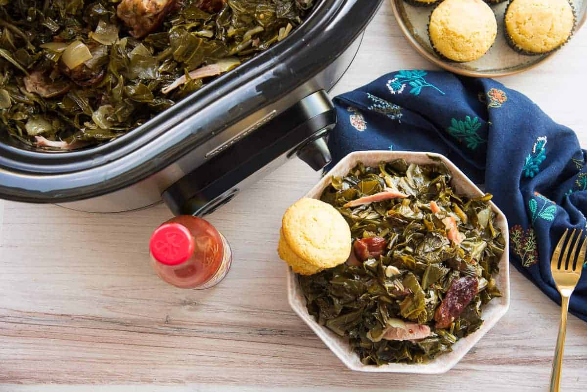 Overhead horizontal image of a pink hexagonal bowl of country style slow cooker collard greens with a cornbread muffins next to a red capped hot sauce bottle.