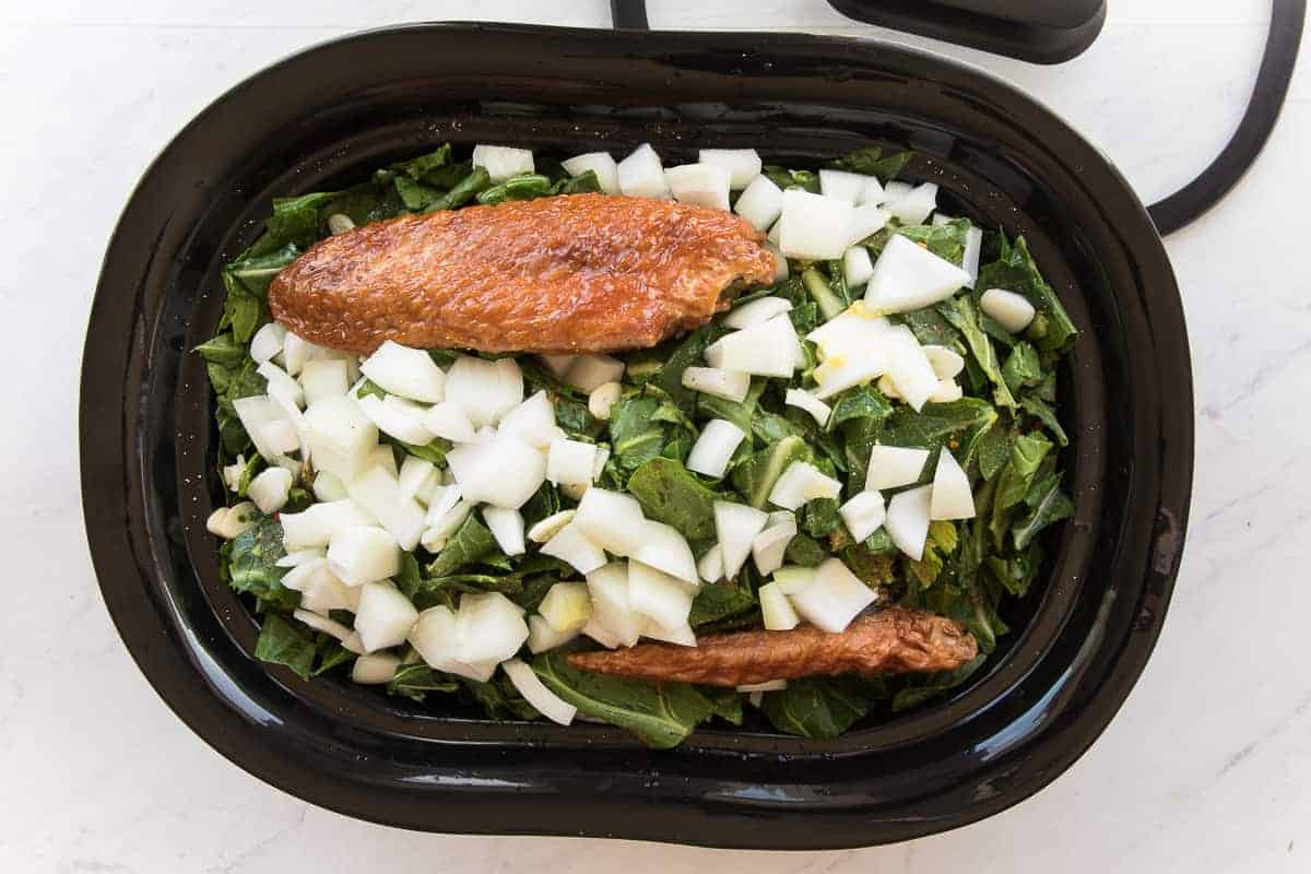 The crockpot with smoked turkey and white onions before cooking.