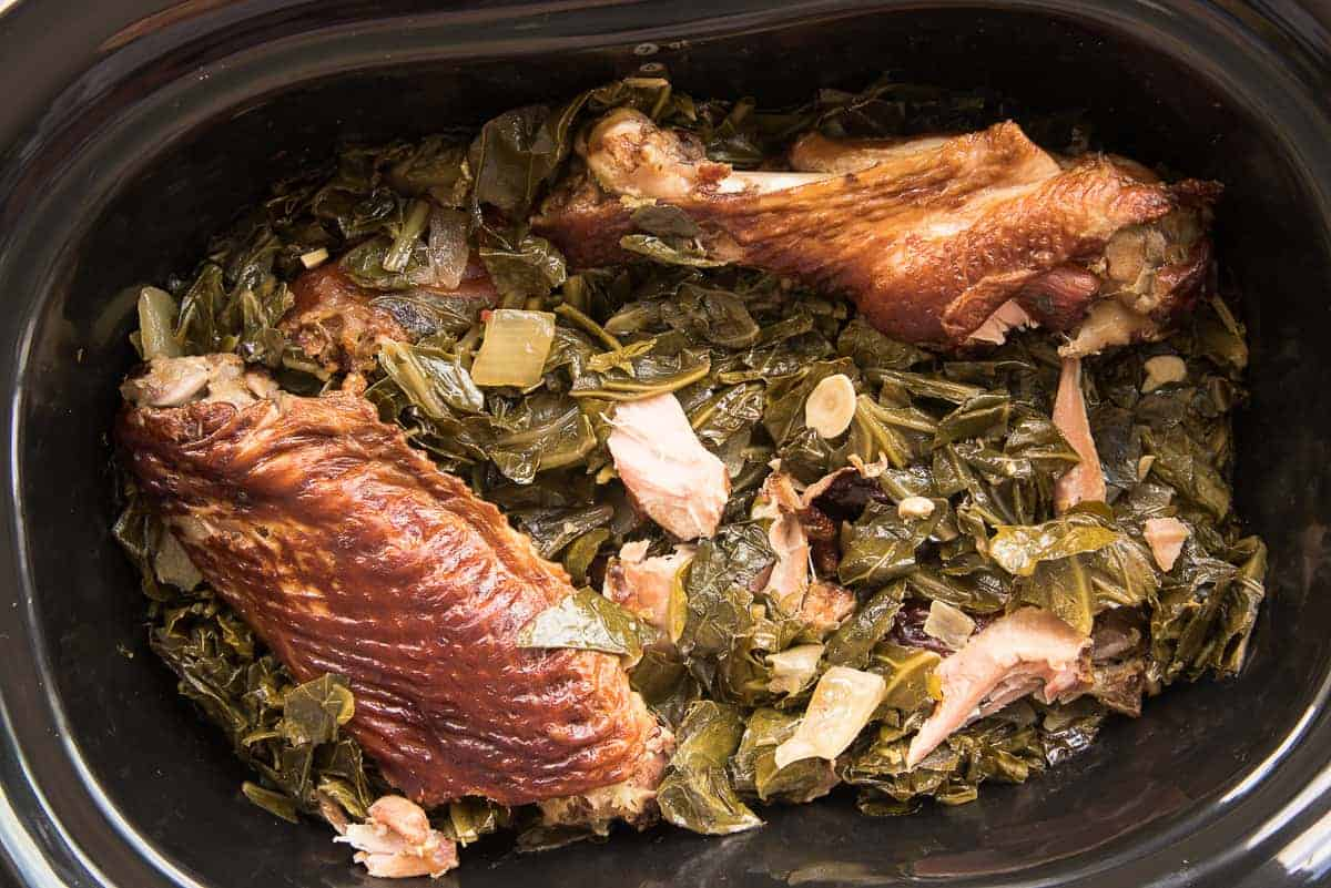 The greens are done cooking in the slow cooker. A smoked turkey wing and leg are on top.