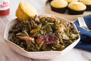 Preview image 2 of a pink bowl of Country Style Collard Greens in the slow cooker with a cornbread muffin.